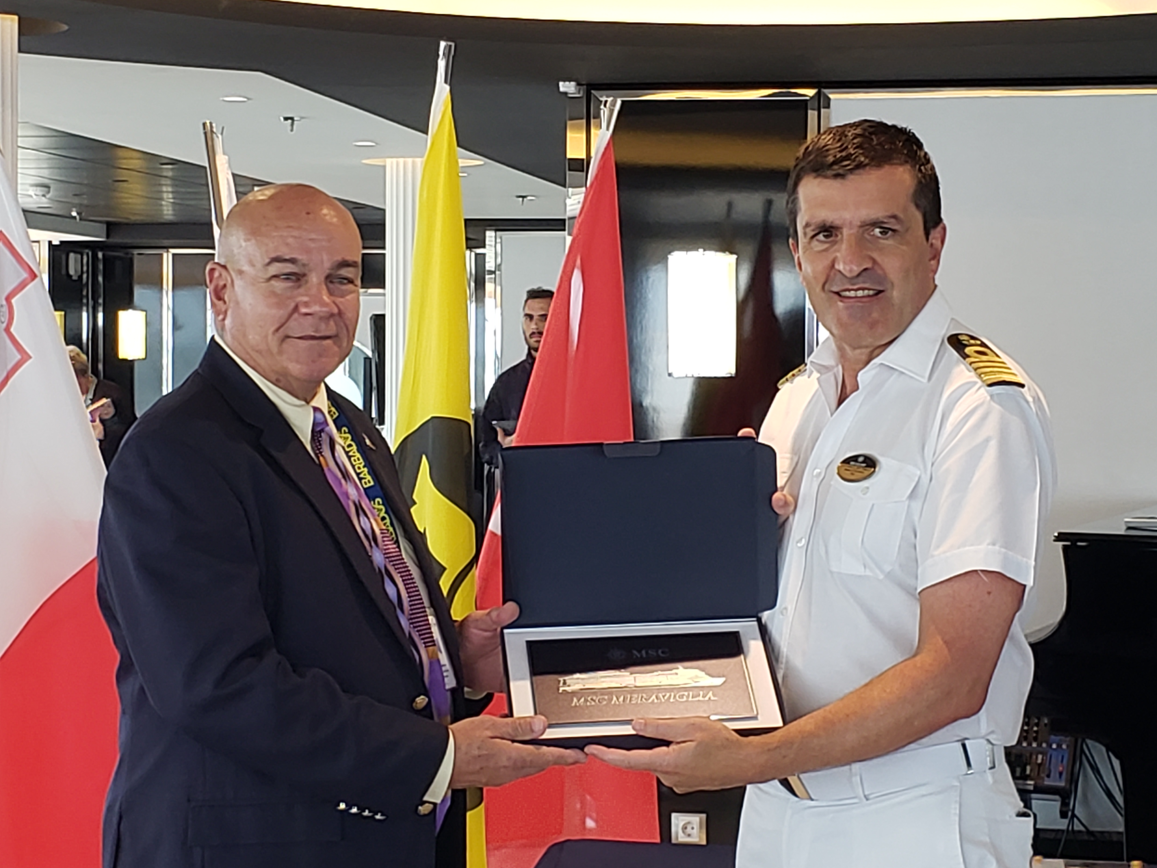 2.	Harbour Master Carl Gonsalves (left) presents the Barbados plaque to captain Stefano Battinelli.